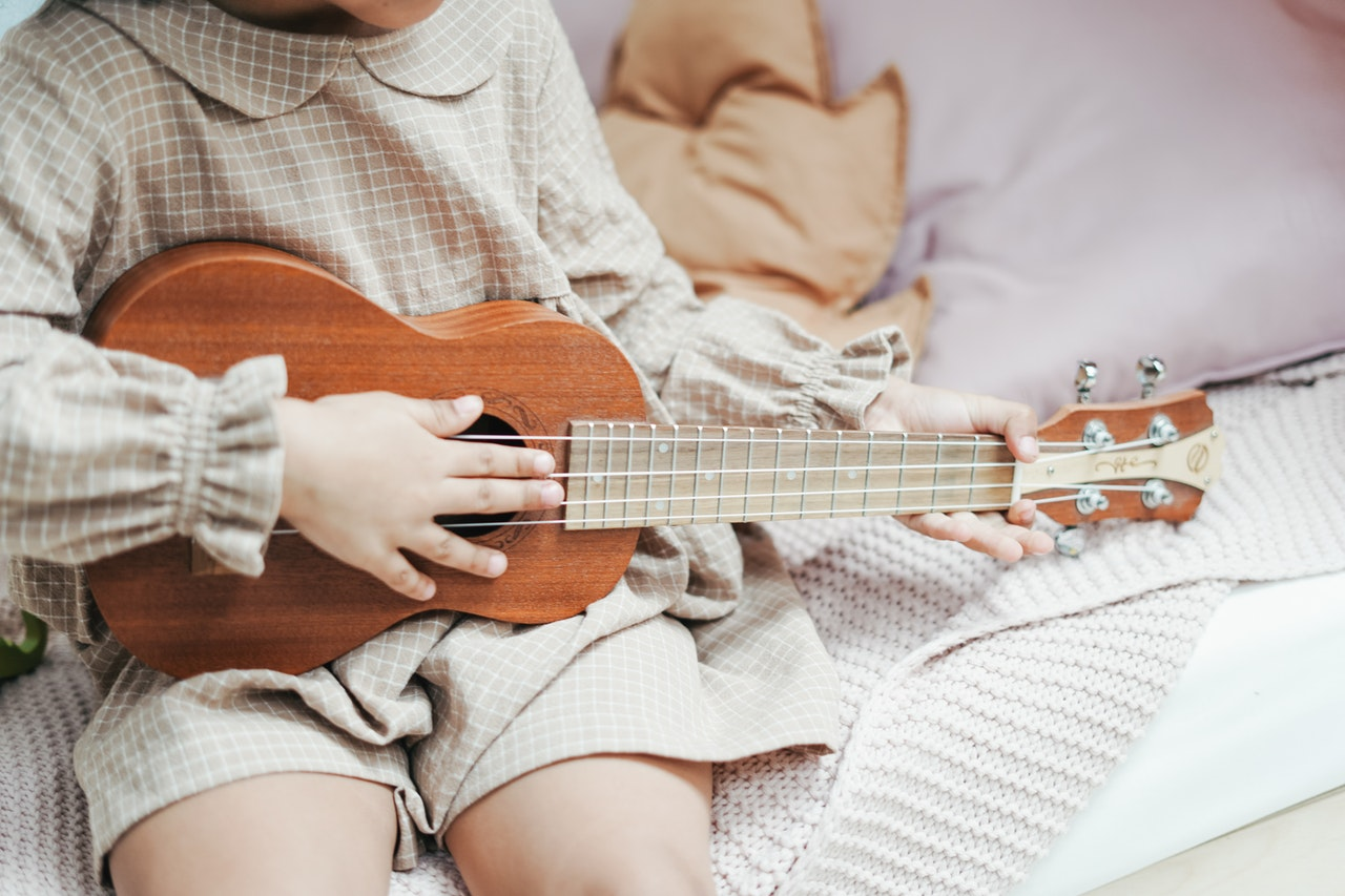 child playing ukelele